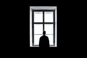 Person feeling lonely in front of a window